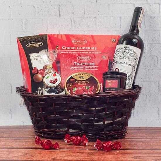 brązowy, wiklonowy kosz prezentowy z winem, słodyczami i owocami w czekoladzie