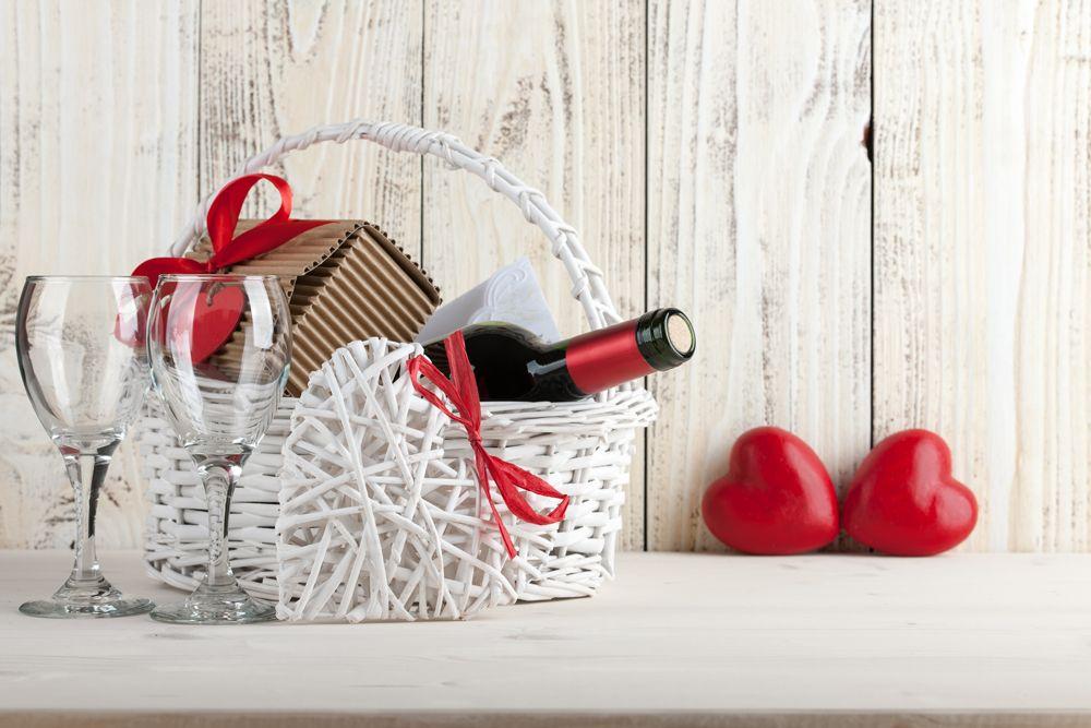 jakie wino na prezent wybrać? biały kosz prezentowy z winem i dwiema lapkami